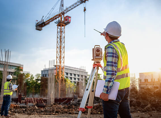 A contractor with DEC Contracting Group, Inc., uses surveying equipment at the construction site of a high-rise office building.