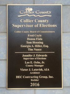 A gold-and-brown plaque naming DEC Contracting Group as the constructors of the Collier County Supervisor of Elections building.