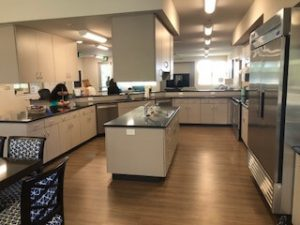 DEC Contracting Group constructed this interior kitchen for Youth Haven, which features a black granite island counter, stainless steel appliances and white cabinetry with ample seating area.